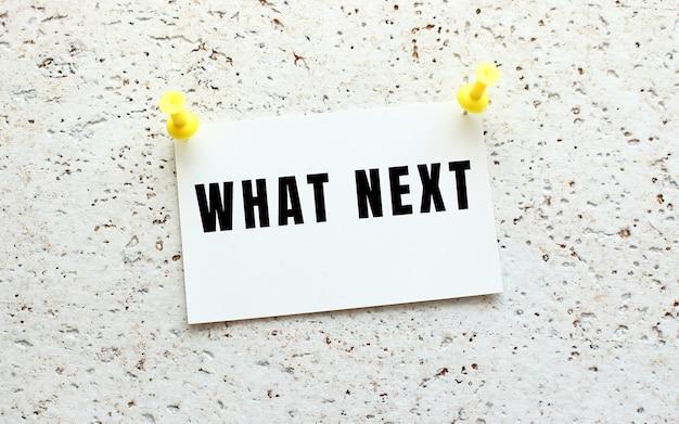 What nextは、ボタンで白いテクスチャの壁に取り付けられたカードに書かれています