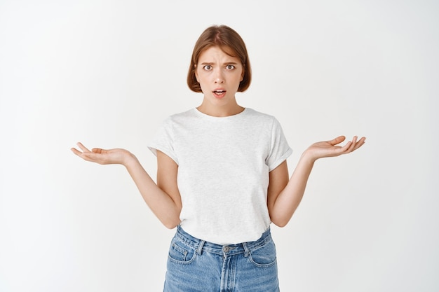 What problem. confused young woman with short hair, shrugging with empty hands sideways, looking concerned and puzzled, white wall