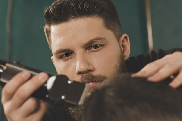 What a professional. cropped closeup of a barber trimming hair of his client carefully