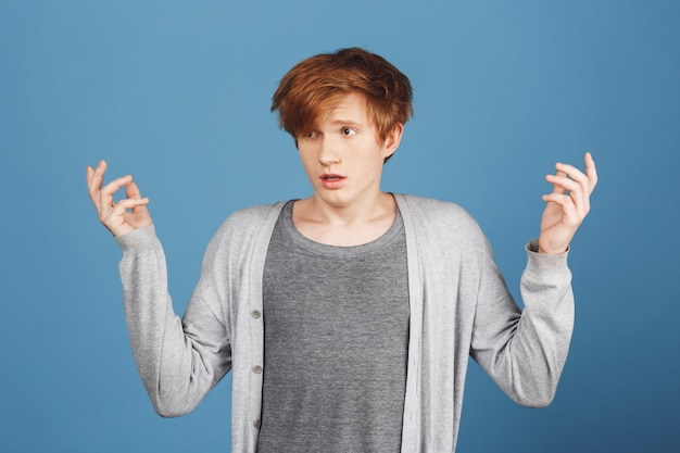 What's going on. young handsome redhead male student in casual grey outfit spreading hands with lost expression, don't understanding what going on on exam