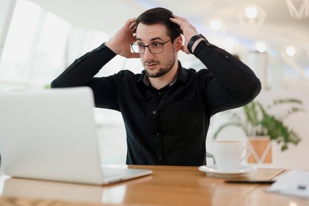 何が起こっていますか?彼のラップトップを見て、彼の手で頭を保持している眼鏡のショックを受けた賢い男。プログラムのエラー。男性プログラマーは、コードにバグがいくつあるかにショックを受けています。