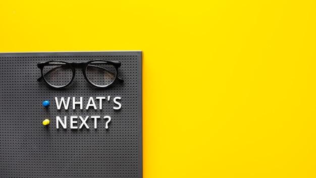 次は何ですか ?作業台に眼鏡をかけたテキスト。研究と新しいものの傾向。起業の概念