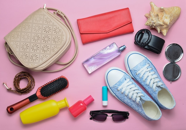 What's in the women's bag? going on a trip. girly fashionable spring and summer accessories: sneakers, cosmetics, beauty and hygiene products, a bag, sunglasses on a pink  pastel background. top view.