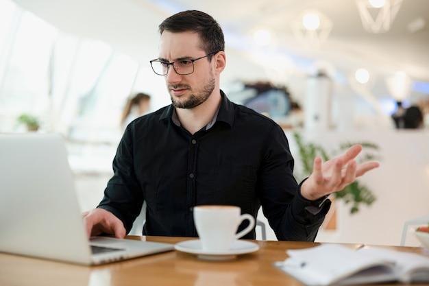 どうしましたか?眼鏡をかけている若い男性のフリーランサーは、彼のコードのどこに問題があるのか理解していません。背景に明るい喫茶店。コミュニケーションの問題。現代のラップトップと一杯のコーヒー。