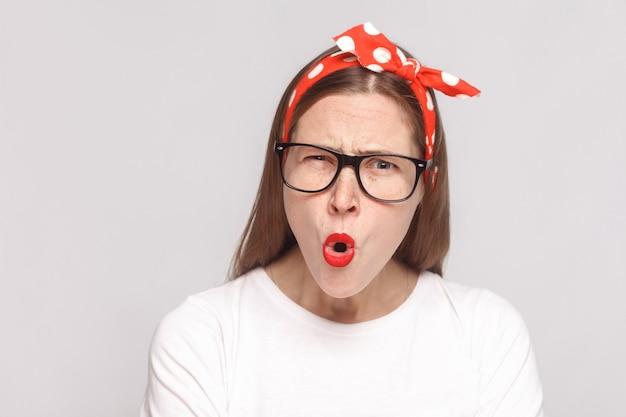 뭐라고 요? 주근깨, 검은 안경, 붉은 입술, 머리띠가 있는 흰색 티셔츠를 입은 아름다운 감정적인 젊은 여성의 놀란 얼굴 클로즈업 초상화. 밝은 회색 배경에 격리된 실내 스튜디오 촬영.