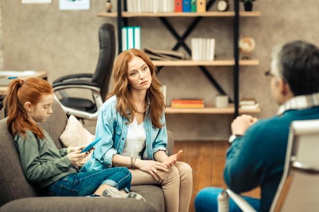 Что мне делать. грустная молодая женщина смотрит на своего врача, спрашивая у него совета