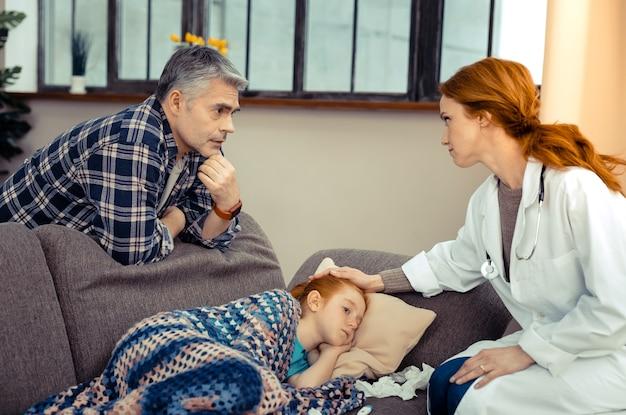 私は何をすべきか。医者の話を聞きながらソファの後ろに立っている真面目な白髪の男