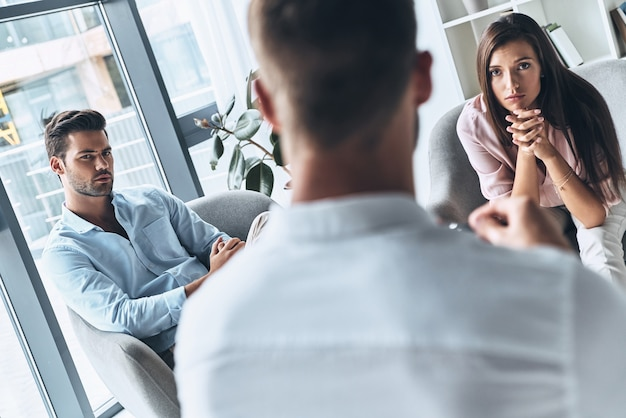 What should we do? young married couple looking at psychologist while sitting on the therapy session
