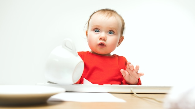 What surprised child baby girl sitting with keyboard of modern computer or laptop in white studio