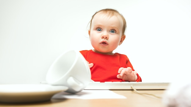 What surprised child baby girl sitting with keyboard of modern computer or laptop in white