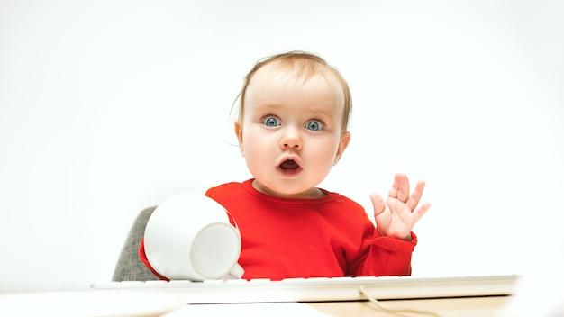 Чем удивлен ребенок девочка сидит с клавиатурой современного компьютера или ноутбука в белой студии