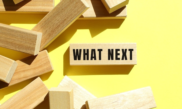 What next text written on a wooden blocks on a yellow background