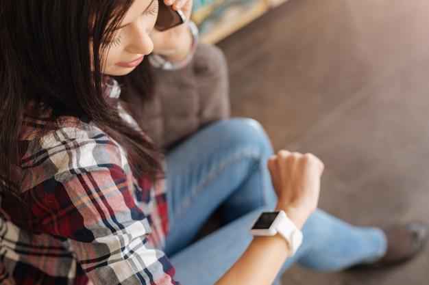 Который сейчас час. красивая милая приятная женщина смотрит на часы и проверяет время во время телефонного разговора со своим другом