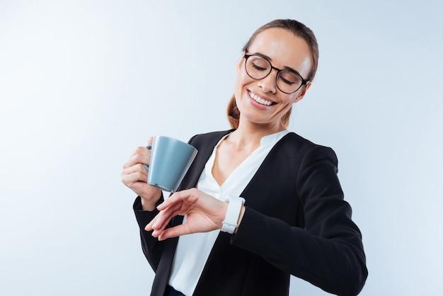 지금 몇 시지. 차 한 잔을 들고 시간을 확인하는 동안 그녀의 시계를보고 즐거운 좋은 긍정적 인 여자