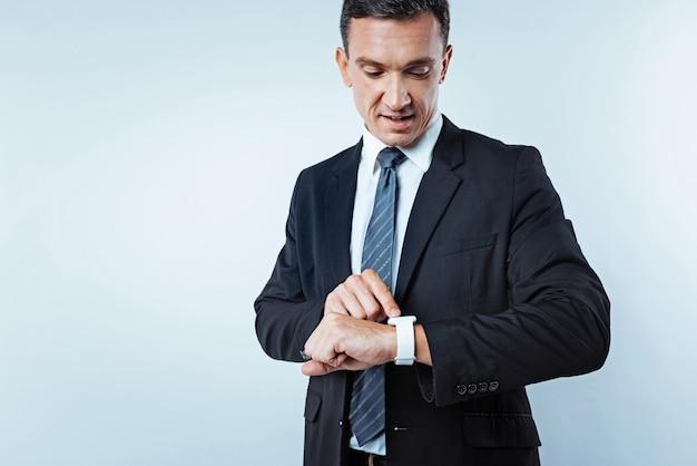 今何時ですか。背景の上に立って仕事に急いでいる間、彼の腕時計のダイヤルを見ている成功した男性の腰のショット。