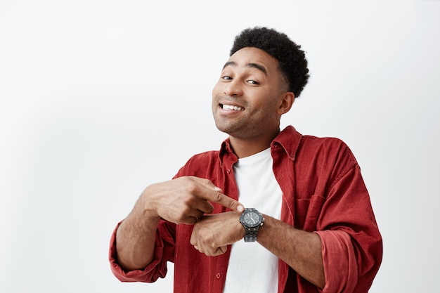 What time is it. portrait of young attractive dark-skinned man with dark afro hairstyle in white t-shirt and red shirt pointing at hand watch with happy face expression, showing it time to eat.