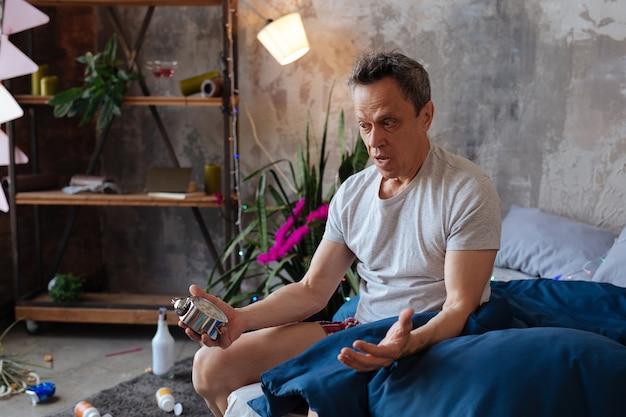 何時に。ベッドに座って時計を保持しているショックを受けた成熟した男