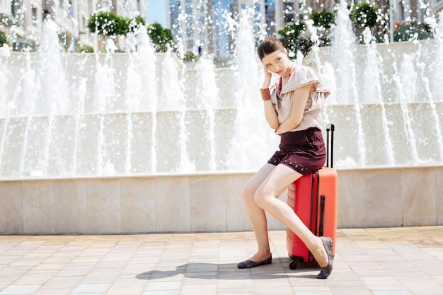 何をすべきか。彼女の友人を待っている間彼女のスーツケースに座っている素敵な悲しい女性