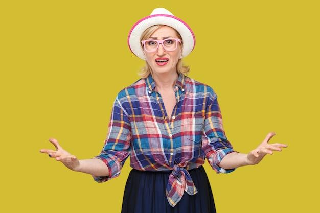 Какие? кто? как? почему? портрет смущенной грустной стильной зрелой женщины в повседневном стиле с шляпой и очками, стоящей с поднятыми руками, сердитой и спрашивающей. закрытый студийный выстрел изолирован на желтом фоне