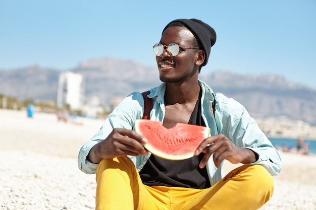 What a wonderful day! happy young afro american tourist wearing trendy clothing eating ripe watermelon, sitting on beach with blurred city