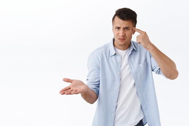 Cosa c'è di sbagliato in te. ritratto di uomo frustrato e infastidito tenere il dito contro la testa e sembrare perplesso, alzare la mano costernato, rimproverare la persona che è pazza, comportarsi in modo strano o stupido, muro bianco