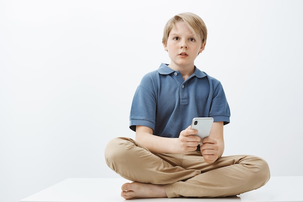 What do you mean no sweets. portrait of questioned curious cute boy with blond hair sitting on floor with crossed feet, holding smartphone and staring aside confused