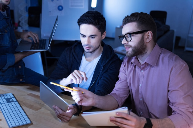 What do you think about this. serious handsome bearded man holding a pencil and pointing with it at the tablet screen while discussing a project with his colleague
