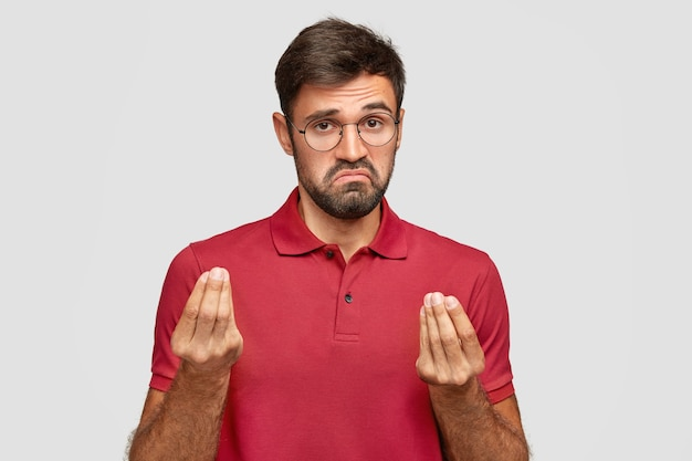 What do you want from me? bearded young male with displeased expression, shows italian gesture wtf, wears spectacles and red t-shirt, stands over white wall. man shows interrogative gesture