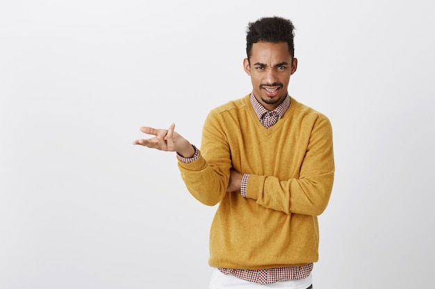 What do you want from me. portrait of outraged clueless young guy with afro haircut and stylish outfit raising palm and shrugging, frowning with displeased expression, being unaware, arguing