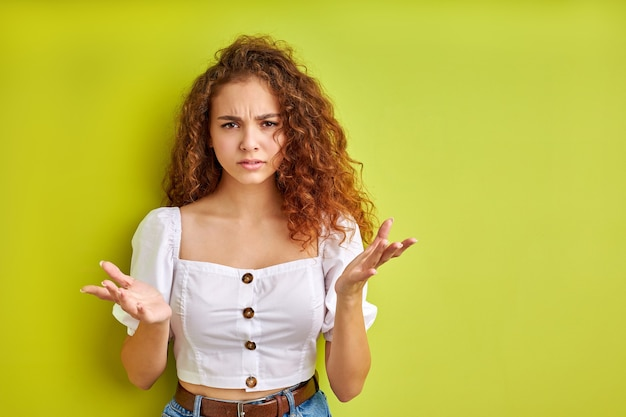 What do you want portrait of confused frustrated girl isolated on green space, angry curly female stand with indignant expression, asking why misunderstanding