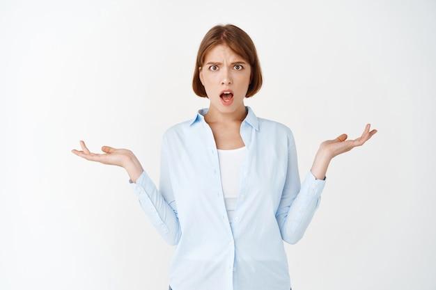 В чем проблема. смущенная и шокированная молодая женщина не может понять, почему, подняв руки вверх и разочарованно открыв рот, стоит на белой стене