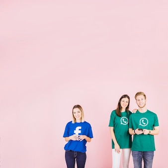 Пара, носить футболку whatsapp, стоящую помимо женщины, носящую facebook top