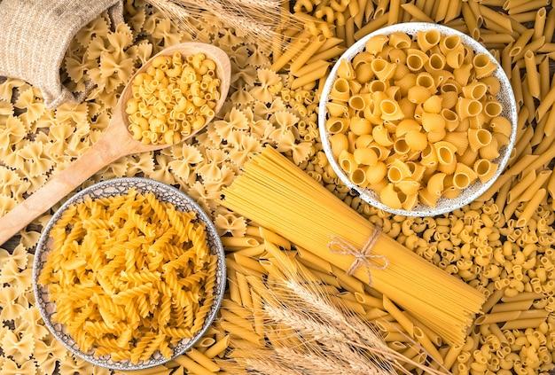 Пшеница и много разных видов макарон на столе.
