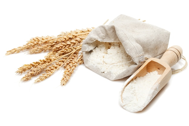Wheat in bag and scoop isolated on white table