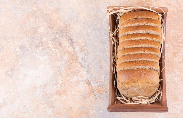 Pane di grano in una scatola, sul tavolo di marmo.