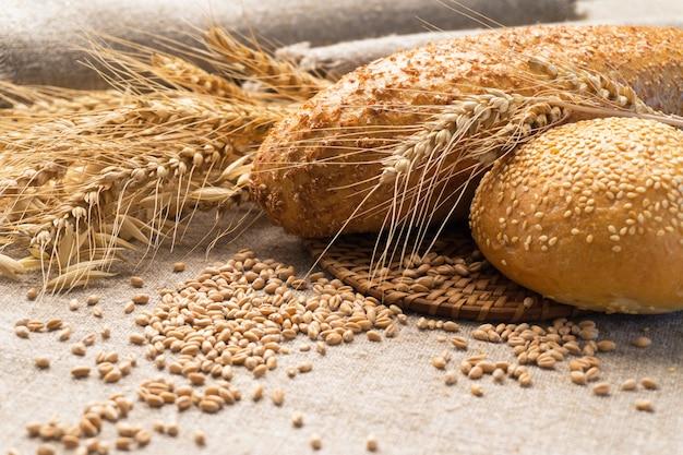 Wheat bread, ears and grain on sackcloth.