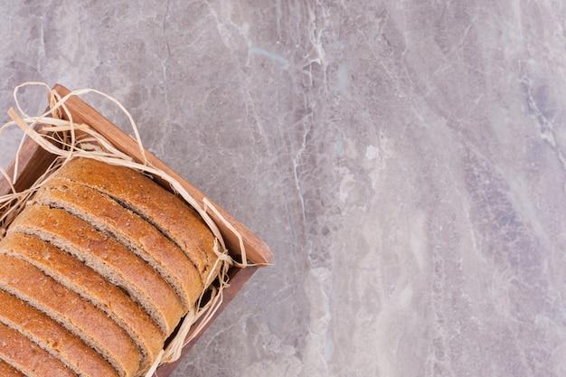 Пшеничный хлеб на соломе в ящике, на мраморном столе.