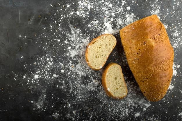 小麦パンのスライスと小麦粉を地面に