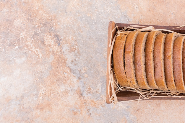 Wheat bread on a straw in a wooden box, on the marble background.