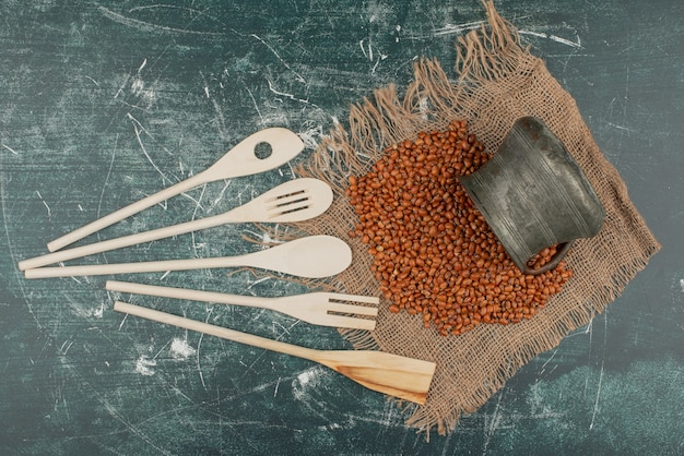 Wheat on burlap with kitchen tools on marble surface.