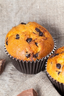 チョコレートを詰めた小麦ケーキ、チョコレートドロップを使ったおいしいベーキングフード、テーブルの上のチョコレートケーキのクローズアップ