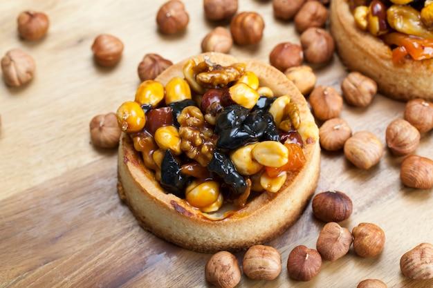 ナッツとドライフルーツのクリームキャラメル入り小麦生地タルト、甘いフィリングの小麦タルト、ヘーゼルナッツ、ピーナッツ、その他の材料を使ったクリスピータルト
