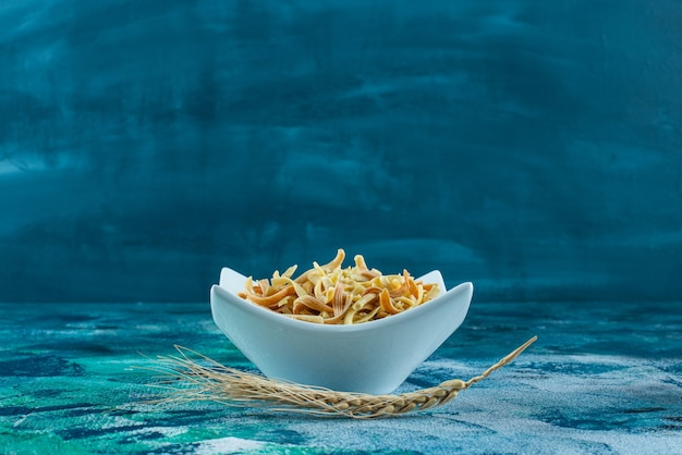 Wheat ear and a bowl of homemade noodle , on the blue background.