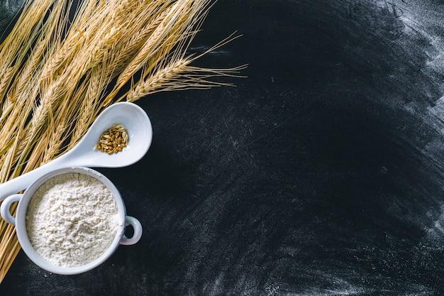 Колосья пшеницы и мука на черном фоне