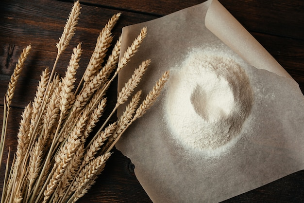 小麦の耳と暗い背景の木のトレーシングペーパー上の小麦粉