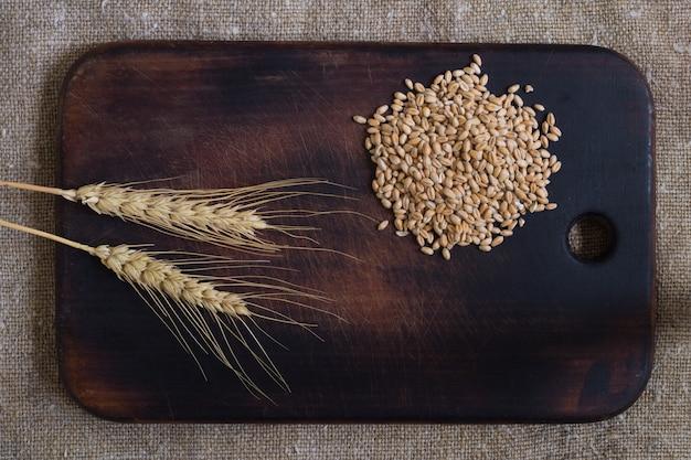 解任の背景のキッチンボード上の小麦の耳と穀物。上面図