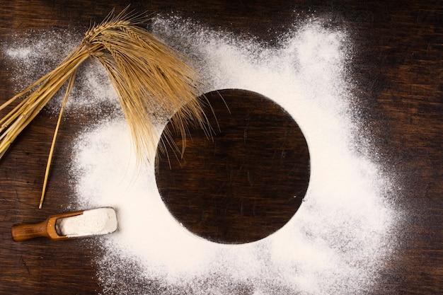 Колосья пшеницы и пшеничная мука, разбросанные по столу