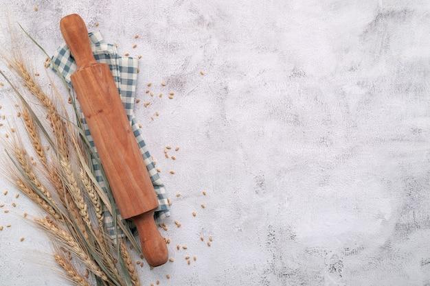 밀 귀와 밀 곡물 설정 흰색 콘크리트 바탕에 롤링 핀.