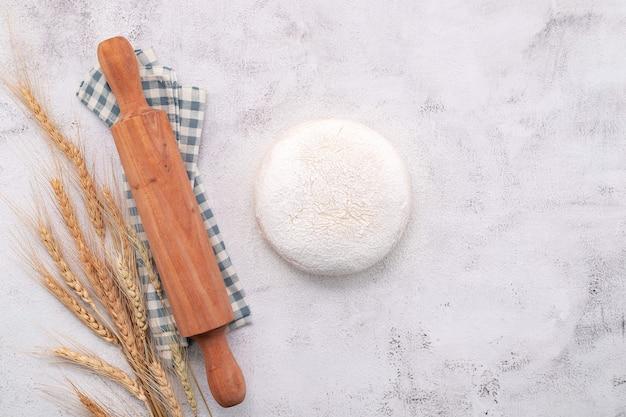 Колосья пшеницы и установка зерен пшеницы со скалкой на белом фоне бетона.