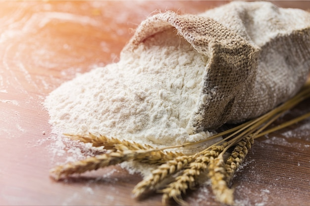 Wheat ears and flour on  background